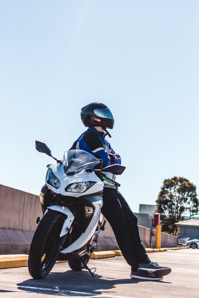 Homme accoudé sur une moto blanche